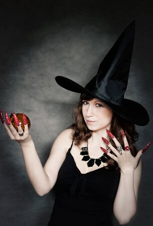 Pretty young witch with black hat, long nails and crystal ball Stock Photo - 10602926
