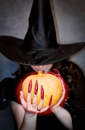 Pretty young witch with black hat, long nails and pumpkin Stock Photo - 10602928