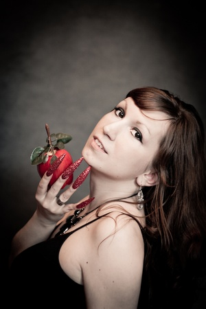 Pretty young lady with red apple and long nails photo