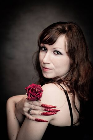 Pretty young with crimson rose and long nails Stock Photo - 10602929