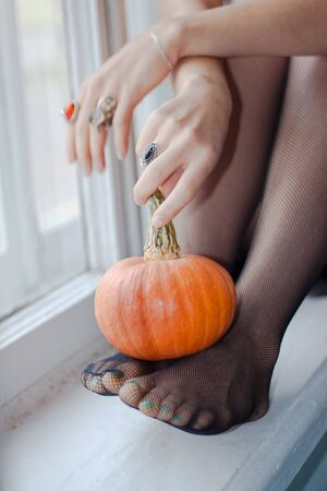 Young lady is seating on the window with small pumpkin Stock Photo - 10689723