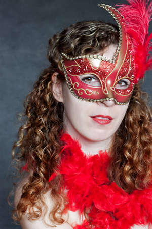 Beautiful young lady in a red mysteus venetian mask Stock Photo - 12776232