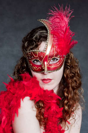 Beautiful young lady in a red venetian mask photo
