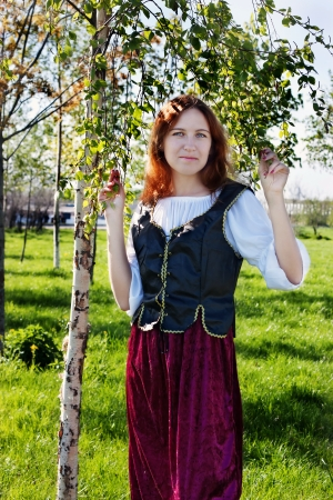 Medieval woman standing near the birch