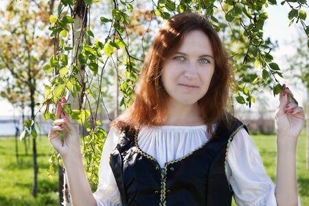 vestido medieval: La mujer medieval de pie cerca de los abedules