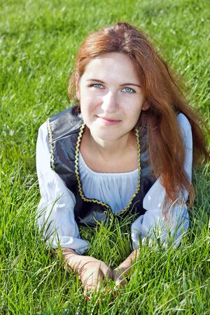 Medieval woman laying on the grass photo