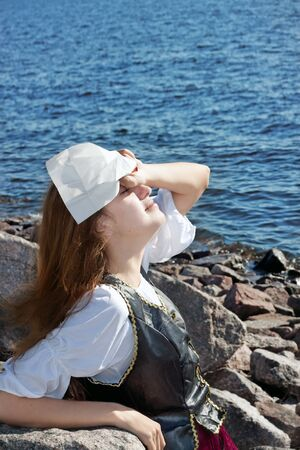 Young medieval woman on the rock near the sea photo