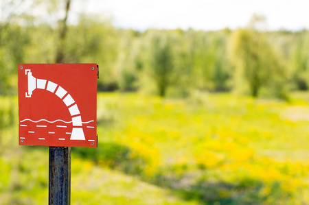fire extinguishing: Water sampling point on yellow dandelion background. Sign for a fire - extinguishing water Stock Photo