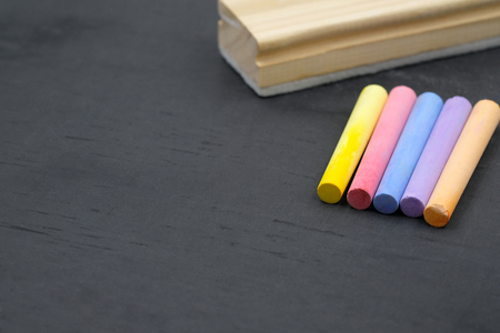 color chalk and eraser with space for text on blackboard