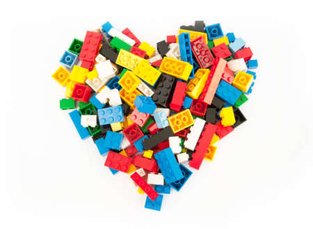 heart form by the pile of  plastic toy block on white floor