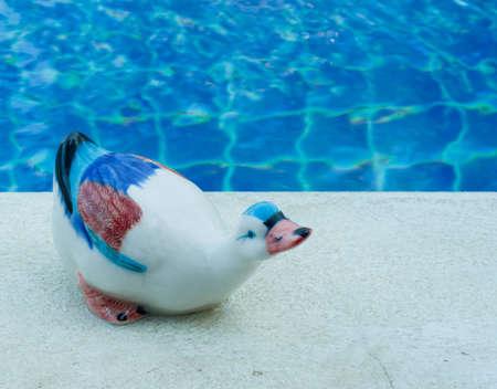 ceramic duck on swimming pool edge Stock Photo