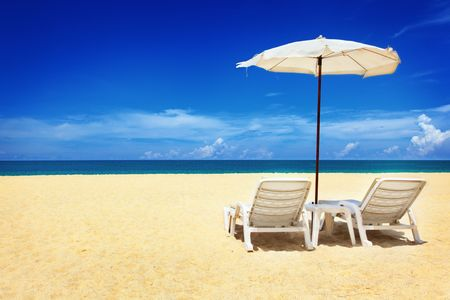 lounge chairs: Two chairs and umbrella on the beach Stock Photo
