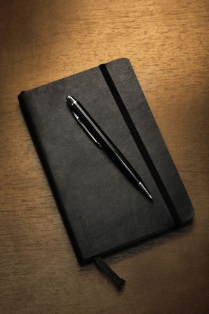 hard bound: Black notepad and pen on table