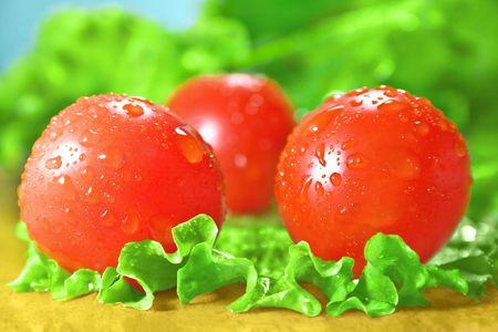 Tomates cerises et la laitue sur une planche à découper.
