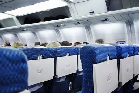 seating: The interior of an airplane cabin with seats and passengers Stock Photo