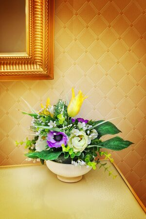 Vase of flowers near mirror on a table photo