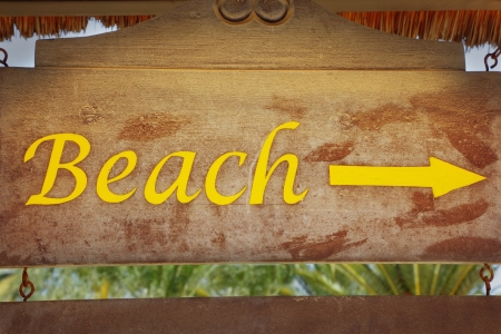 Sign pointing direction to beach and night club photo