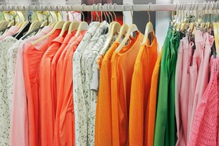 ropa colgada: Una hilera de ropa colgada en el estante