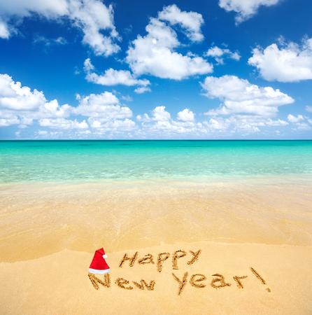 sun beach: Happy New Year written on a sandy beach Stock Photo