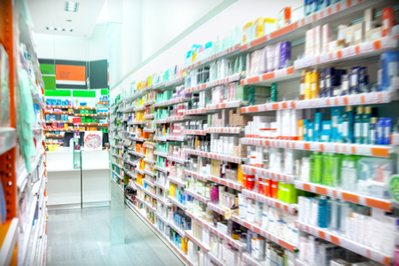 Medicines displayed at pharmacy, abstract blurred focus.