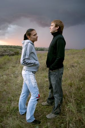 Young couple standing together on the field before a storm photo