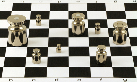 objects: Set of shiny metal weights on chessboard surface. Each weight is disposed in own chess square. Group of eight objects.