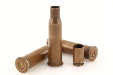 casings: Three 7.62 mm caliber rifle and one 9 mm caliber pistol old bullet casings on a light background with slight mirror reflections on a background surface. Focus on full depth.