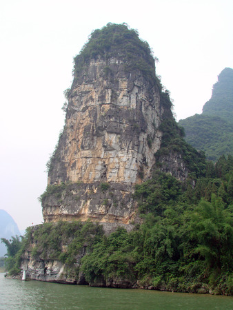 Steep and beautiful mountain peak by the side of Li river passing thru Guilin city of China photo