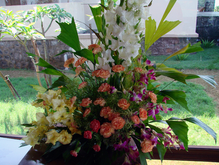 comprising: Decorative flower arrangement comprising of roses, orchids and such other colorful fresh blooming flowers