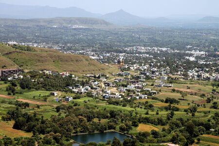 adds: panoramic view of a beautiful town surrounded by mountains and hills. lake adds to its beauty and houses are amidst trees n fields