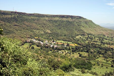 locality: Serene life of a small locality surrounded by lush green trees and hills Stock Photo