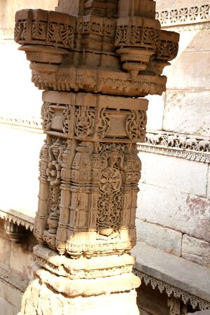 monument in india: sunlight and shade adding to the beauty of a well carved pillar of an ancient monument called Adalaj Step-well in India