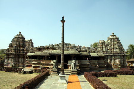 Front view of beautiful ancient Veer Narayana Temple at Belavadi in the State of Karnataka in India. Tall religious pillar on the outside is also prominant Stock Photo