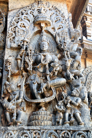 either: Carving on the walls of an ancient temple at Bellur in India, of a Hindu Godess and her devotees on either side Stock Photo