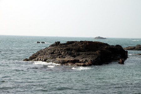 volcanic eruption: small island of hexagonal shaped rocks, formed naturally as a result of volcanic eruption. The small island formed in the sea in the Southern part of India