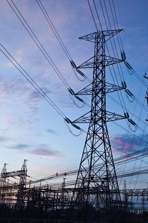 Wysokie słupy energetyczne napięcia i błękitne niebo rano