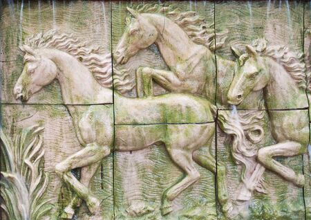 Horses in low relief statue cut out as jig saw image and water fall in front of. photo