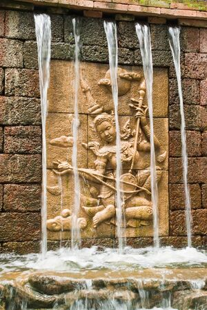 Fairy in low relief statue cut out as jig saw image and water fall in front of. photo