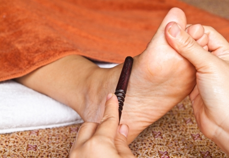 reflexology foot massage by stick wood, spa foot treatment,Thailand photo