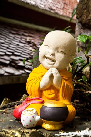 Doll clay monk smiling used in ornamental gardens in Thailand  photo
