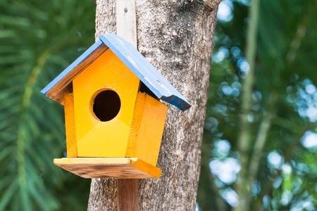 yellow birdhouse on a tree