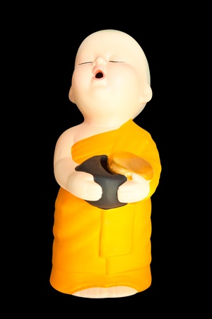 alms: Doll clay baby monk with  alms bowl isolated on black background