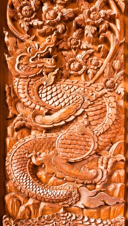 Traditional Thai style wood carving as dragon on the window of church, photo