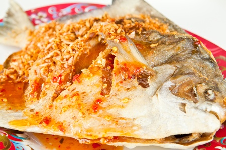 Fried fish with sauce,sour and spicy on white plate,Thai style food.  photo