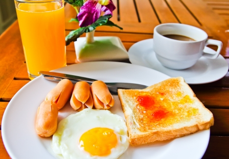 breakfast with fried eggs,sausage, toasts, juice and coffee  photo