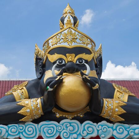 Statue of black deity called Rahu and blue sky background. Stock Photo - 17561691