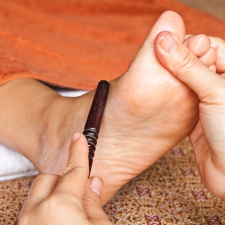 restore energy flow: reflexology foot massage by stick wood, spa foot treatment,Thailand