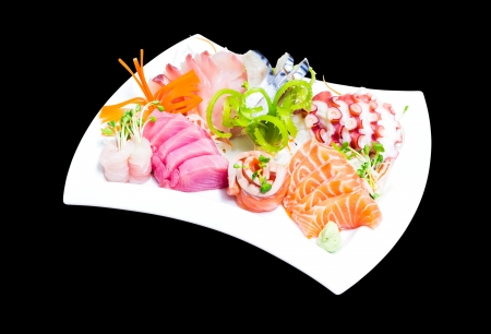 Mixed sashimi in white plate isolated on black background photo