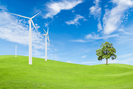 windturbine: wind turbine and tree on green grass with blue sky background used for green earth concept Stock Photo