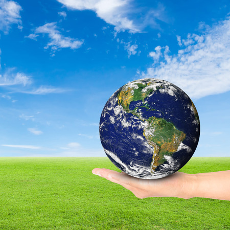 photoelectric: Green Earth concept,hand holding earth against green field and blue sky background. Stock Photo